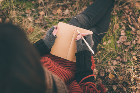 47932030 - woman in nature writing in a notebook